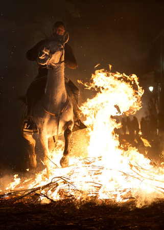 Horse with its rider rapidly breaking through the fire