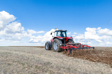 seeding: agricultural machinery in the foreground carrying out work in the field