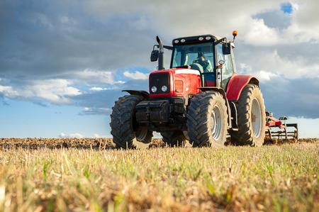 Macchine agricole in primo piano che svolgono lavori in campo Archivio Fotografico - 82343940