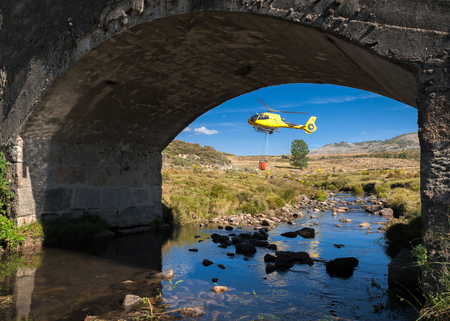 Helicopter on river bed with basket full of water