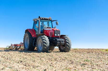 agricultural machinery in the foreground carrying out work in the field