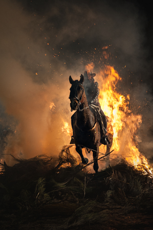 Bonfire with flames and horses traversing above it to purify 스톡 콘텐츠