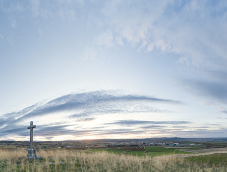 Stone cross in the foreground with background of sky at dusk