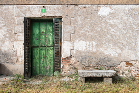 Old wooden door belonging to housing located in country village