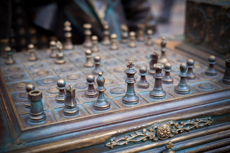 Chess figures made of aged copper in the foreground Banco de Imagens