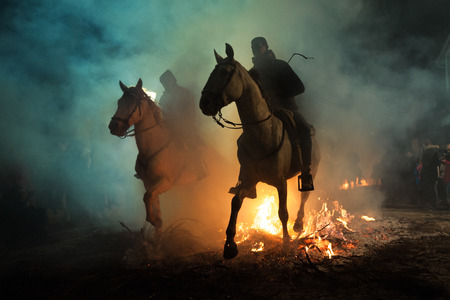 Horse passing over the bonfire of Piornos, as a tradition to purify the soul of animals, in the celebration carried out in the town of San Bartolomé de Pinares, province of Avila, Spain, on January 16 新聞圖片