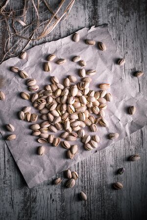 pistachios on wooden table in the foreground with darkened background Standard-Bild - 134863203