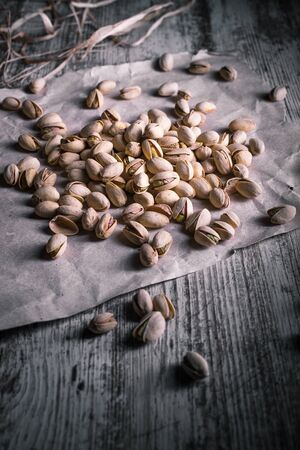 pistachios on wooden table in the foreground with darkened background Standard-Bild - 134863207
