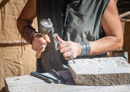 stonemason working with his tools, focused in the foreground with medieval attire