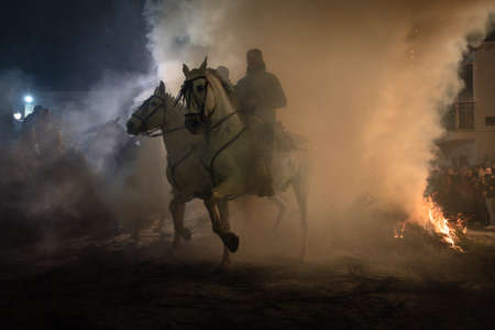 rider riding his horse, jumping fire fire to purify the animal, in a religious event held in the town of El Herradón de Pinares, Avila, Spain, on January 16, 2020