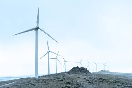 eolic wind mill in the foreground with background in complementary blue and green colours