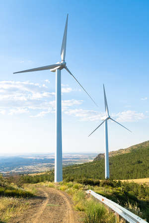 turnina wind in the foreground with green countryside and bluish sky
