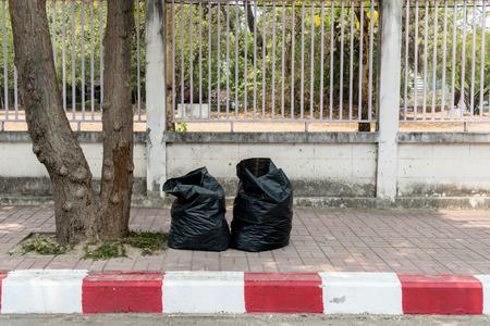 garbage bag: Black garbage bag beside road
