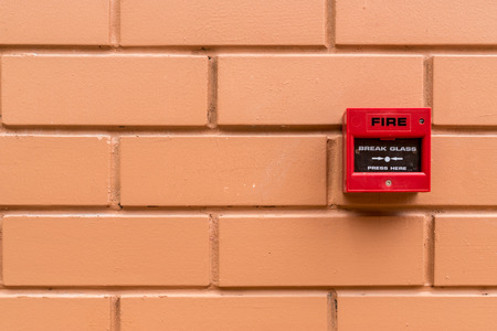 sprinkler alarm: Red fire switch on brown brick wall Stock Photo