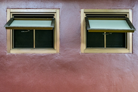 an awning: Awning windows on brown concrete wall