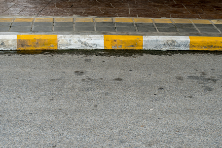 curb: Concrete sidewalk with yellow and white curb Stock Photo