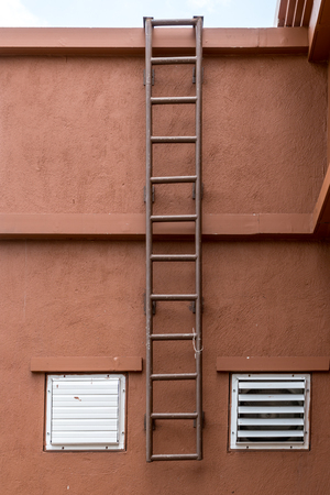 metal grunge: Iron fixed ladder on brown concrete wall Stock Photo