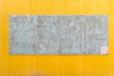 cracked cement: Cracked cement board on yellow concrete wall