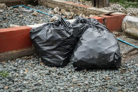 garbage bag: Black garbage bag on gray gravel sidewalk