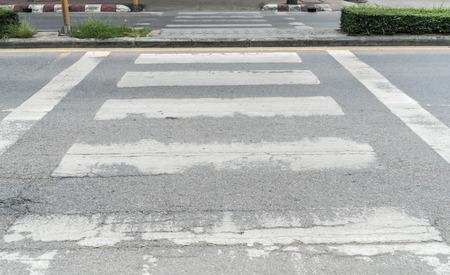 paso de peatones: Fading señal de paso de peatones en la carretera de asfalto