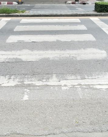 paso peatonal: Fading señal de paso de peatones en la carretera de asfalto