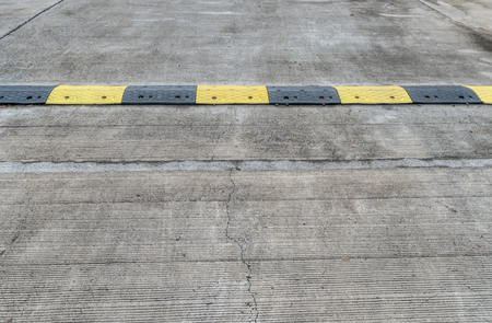 bump: Yellow and black speed bump on concrete road