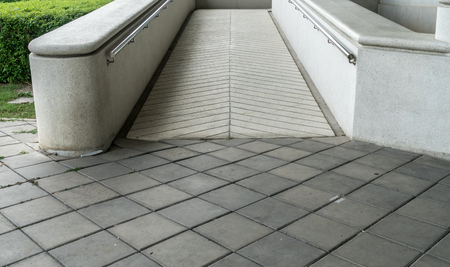 disablement: Concrete ramp for wheelchair with trimmed plants