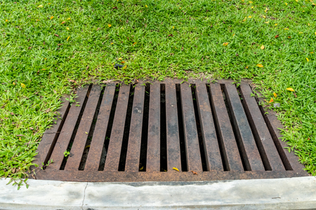 Rusty metal drain cover with green grass Stock Photo