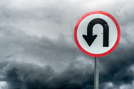 U turn sign on white dark cloud background with clipping path