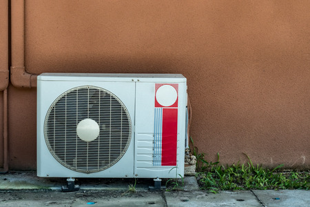 condenser: Condenser unit of Air condition on brown wall