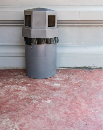 wastebasket: Gray trash can on concrete wall background Stock Photo