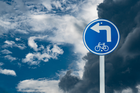 turn left sign: Turn left sign for bicycle on separate dark and white cloud