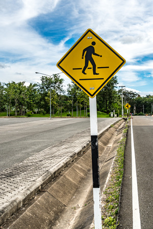 law school: Yellow pedestrian sign on the side of asphalt road