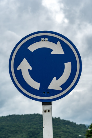 roundabout: Blue roundabout traffic sign on cloud background