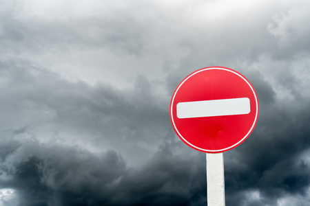Do not entry traffic sign on dark cloud background Stock Photo