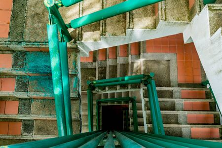 Old concrete staircase with green pipe railing