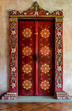 Red wooden Thais old style doors with brown tiles floor
