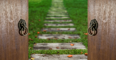 Manija del viejo estilo en la puerta de madera marrón con el camino de madera y la hierba verde Foto de archivo - 83008398