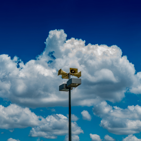 Beige horn speaker on cloudy background Stock Photo