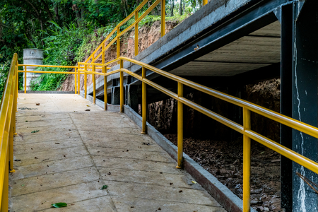Concrete ramp for wheelchair with yellow iron railing in the park