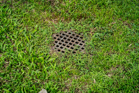 Rusty metal drain cover on green grass Stock Photo
