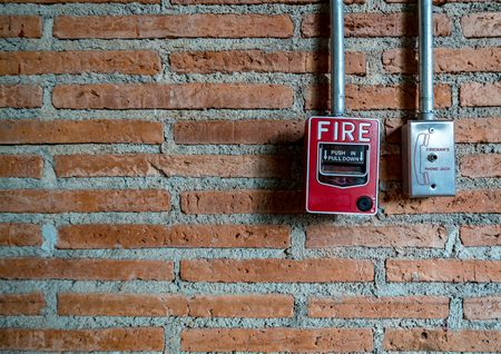 Red fire switch on brown brick wall Imagens