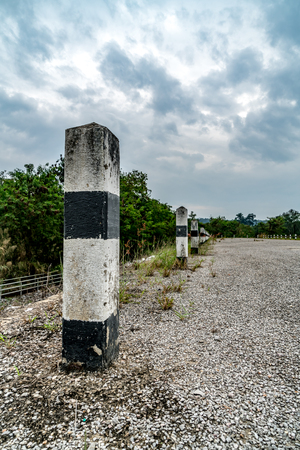Black and white concrete traffic pole on country road Stock Photo