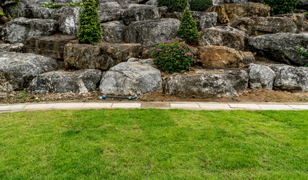 Superbe Rock Garden With Green Lawn And Concrete Water Drain Cover In The Park  Stock Photo