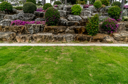 Charmant Rock Garden With Green Lawn And Concrete Water Drain Cover In The Park  Stock Photo