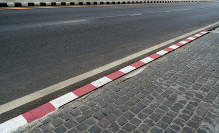 Perspective of Asphalt road with red and white curb