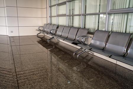 Gray row chairs on brown granite floor