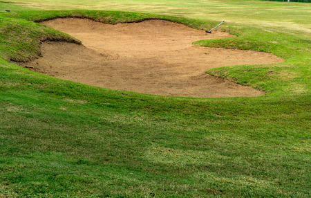 Sand bunker with green lawn in golf course