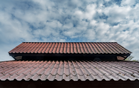 Old brown roof pattern with cloudy blue sky background Reklamní fotografie