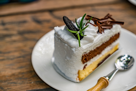 Slice cake with spoon on white plate